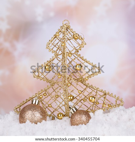 Gold Christmas tree and balls on snow with holiday background - stock photo