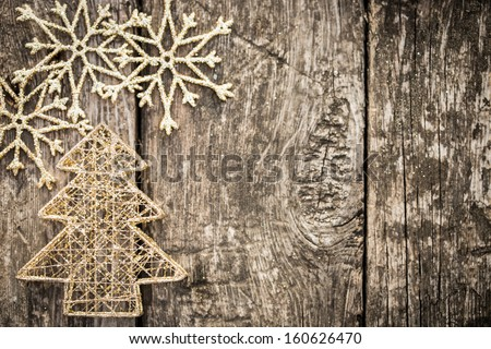 Gold Christmas tree decorations on grunge wood background. Winter holidays concept. Copy space for your text - stock photo