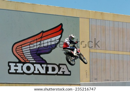 GOLD COAST, AUS - NOV 06 2014:Biker jumps beside Honda Motor billboard.Honda has been the world's largest motorcycle manufacturer since 1959
