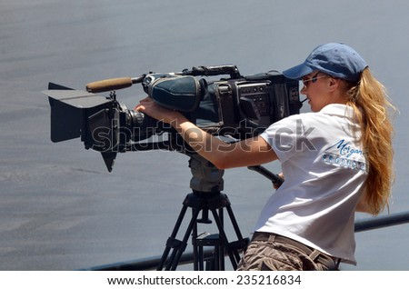 GOLD COAST, AUS - NOV 06 2014:Camerawoman filming. In 2006, there were approximately 27,000 television, video, and motion picture camera operators employed in the United States. - stock photo