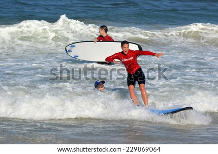 GOLD COAST, AUS - NOV 01 2014:Female wave surfing instructor teaches man and woman how to surf in Surfers Paradise, Queensland, Australia. - stock photo