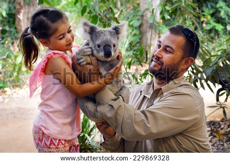 GOLD COAST, AUS - NOV 04 2014:Little girl (Talya Ben-Ari age 05) holding a Koala with Zookeeper in Currumbin Wildlife Sanctuary Gold Coast Queensland, Australia.Koalas cannot be kept legally as pets. - stock photo
