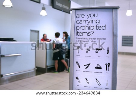 GOLD COAST, AUS - NOV 22 2014:Passengers in check in desk.For the safety and security air travelers airlines have prohibited certain items from brought onto airplanes in carry-on and/or checked bags. - stock photo