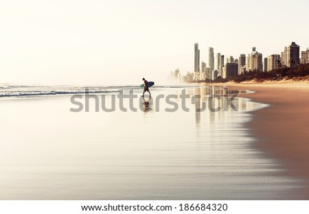 GOLD COAST, AUSTRALIA - JANUARY 2, 2013: Surfer on the beach in City of Gold Coast, Queensland on January 2, 2013, Australia - stock photo