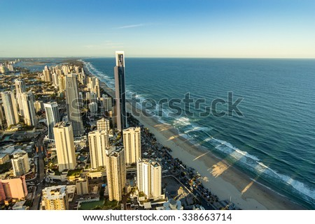 Gold Coast Beautiful Panorama Aerial view of Surfers Paradise City Skyline Cityscape with Shadow from Skyscraper Building on the sea from Q1 Building under Golden Sky Sunset in summer, Australia - stock photo