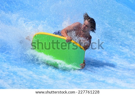 GOLD COAST OCT 29 2014: Man falling from a surfing board on FlowRider. It is a water park attraction that simulate the riding of waves in the ocean - stock photo