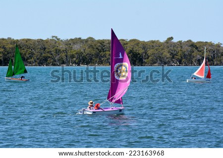 GOLD COAST - SEP 30 2014:People sail a a dingy. With nine times more waterways than Venice, the Gold Coast is a boating paradise with over 260 kilometers of navigable waterways within the city. - stock photo