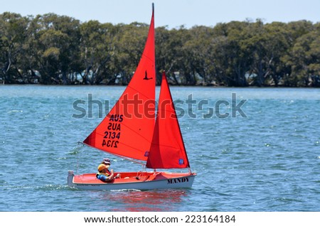 GOLD COAST - SEP 30 2014:Retired couple sail a dingy. With nine times more waterways than Venice, the Gold Coast is a boating paradise with over 260 kilometers of navigable waterways within the city. - stock photo