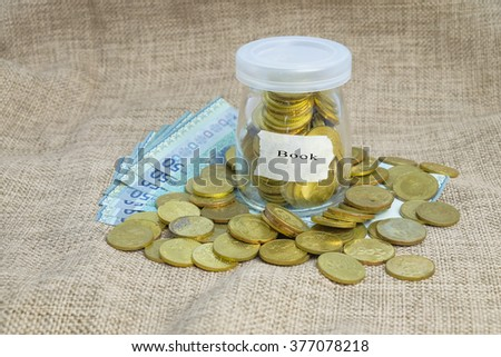 Gold coins in bottle  with word book, Saving concepts - stock photo