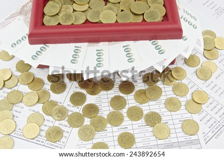 Gold coins on red treasure box and bills place on finance account.