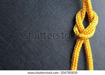 Gold color rope cable with simple knot close up photo hanging down in front of the black color artificial leather background.  - stock photo