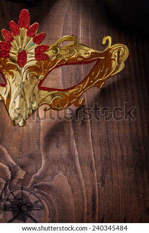 gold colored carnaval mask on old wooden board very close up view - stock photo