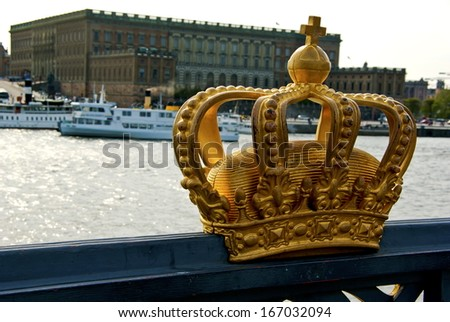 Gold crown on a bridge and the Swedish Royal Palace in Stockholm and tourist boats in background.
