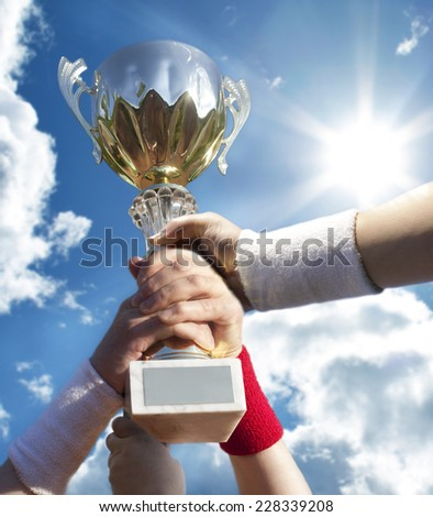 Gold cup in hands . - stock photo
