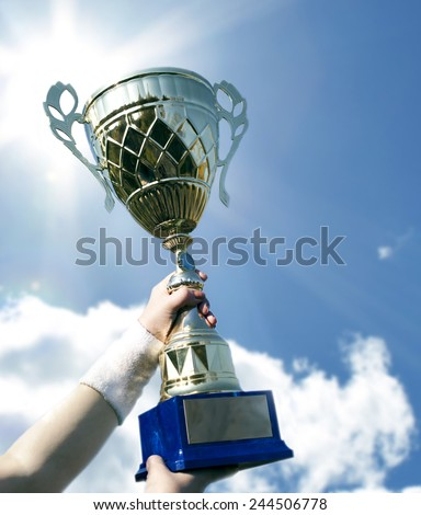 Gold cup in hands of champions against the blue sky. - stock photo