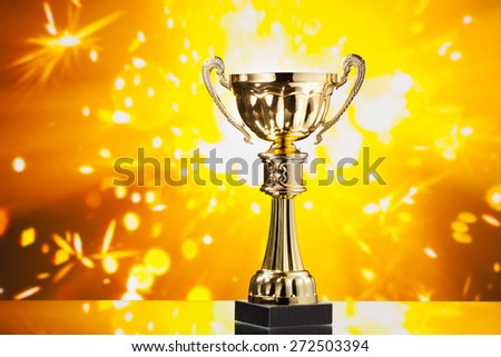 gold cup trophy against shiny sparks background - stock photo