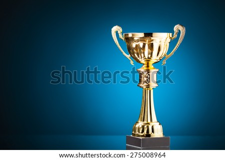gold cup trophy on blue background - stock photo