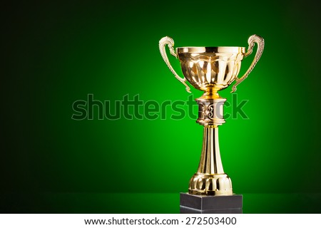 gold cup trophy on green background - stock photo