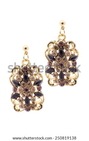 Gold earrings inlaid with  gemstones on a white background - stock photo