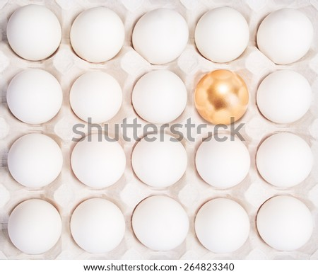 gold Easter egg between many white eggs in container - stock photo