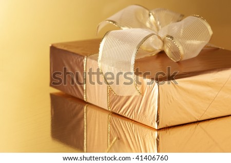 Gold foil gift with gold translucent bow on golden background. - stock photo