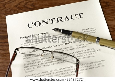 gold fountain pen, glasses and contract on desk