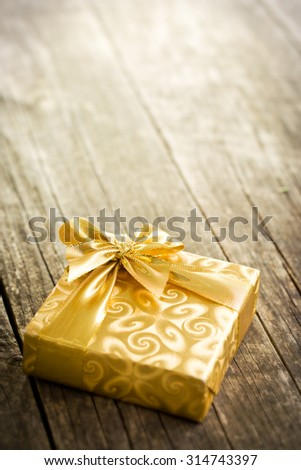 gold gift box on old wooden table