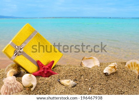 Gold gift box on sand with summer sea background  - stock photo
