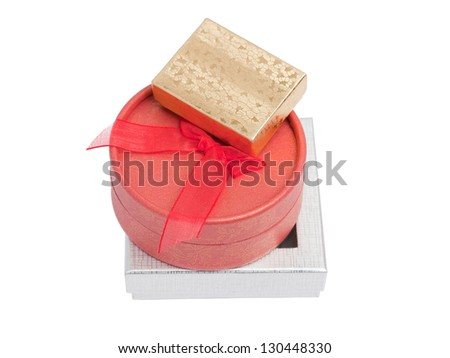 Gold gift box on top round red one isolated