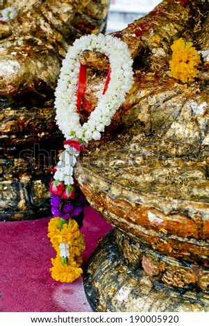 Gold hand of Buddha with flower garland - stock photo