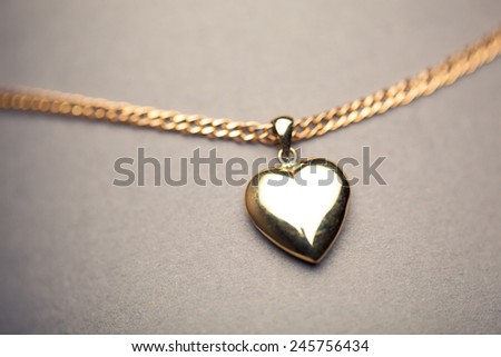 gold heart pendant on grey background - stock photo