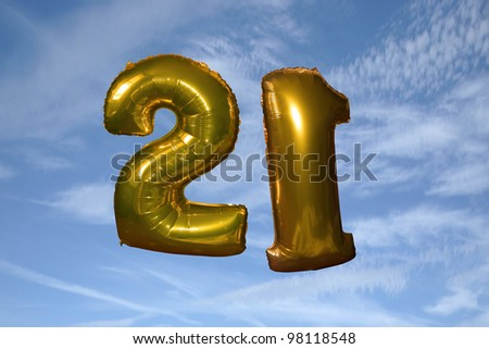 gold helium filled 21st birthday balloons floating in the sky - stock photo
