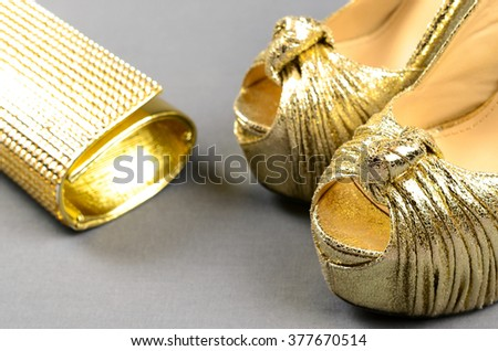 Gold high-heeled shoes and clutch bag on a gray background - stock photo