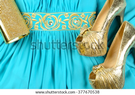 Gold high-heeled shoes, clutch bag and blue dress with gold accentson. Top view - stock photo