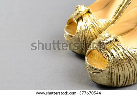 Gold high-heeled shoes on a gray background - stock photo