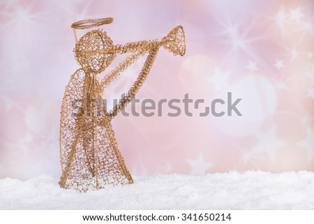 Gold holiday angel figurine on snow with colorful background - stock photo