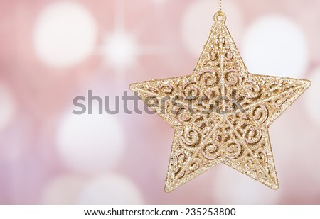 Gold holiday star ornament on a colorful background - stock photo
