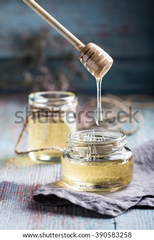 Gold honey in glasses on the blue wooden table