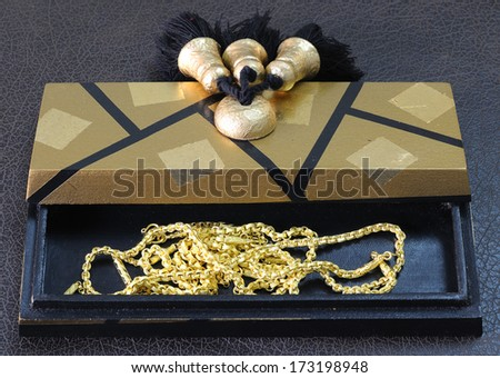 gold in wooden box on the Brown leather - stock photo