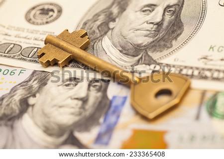 gold key on hundred dollar bills - stock photo