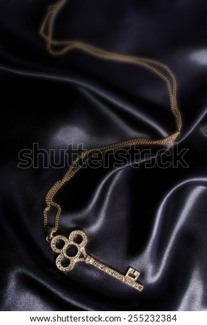 gold key pendant on black silk - stock photo