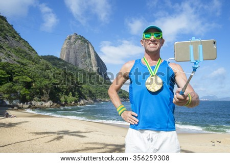 Gold medal athlete posing for a selfie with his mobile phone on a selfie stick at Praia Vermelha Red Beach in Urca, Rio de Janeiro, Brazil - stock photo