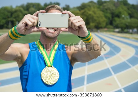 Gold medal athlete smiling at his mobile phone taking a selfie at running track  - stock photo