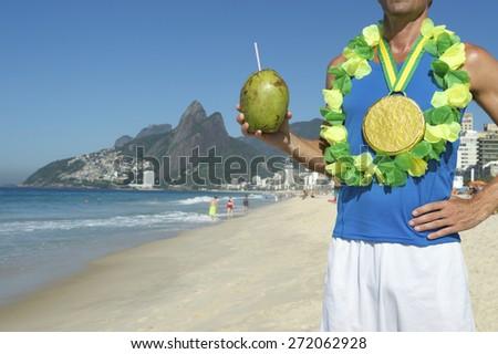Gold medal athlete wearing celebrating winning with coconut on Ipanema Beach Rio de Janeiro Brazil  - stock photo