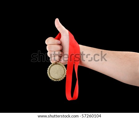 Gold medal in hand isolated on black