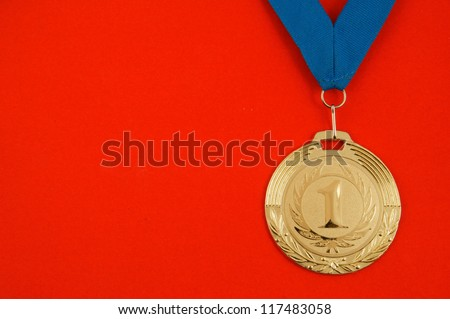 Gold medal with blue ribbon on red velveteen - stock photo