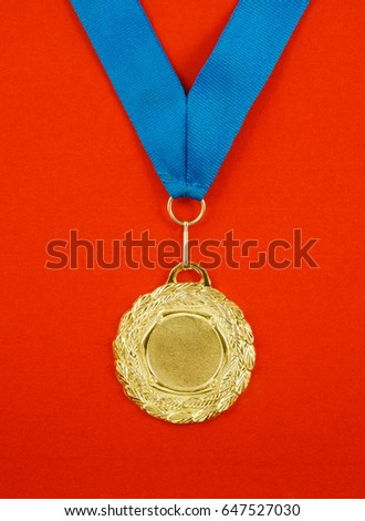 Gold medal with blue ribbon on red velveteen