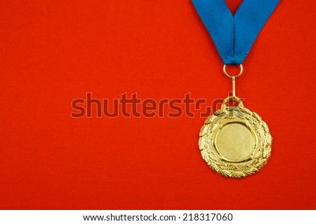 Gold medal with blue ribbon on red velveteen with room for text - stock photo