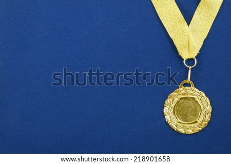 Gold medal with golden ribbon on blue velveteen with room for text  - stock photo