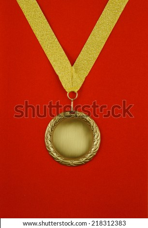 Gold medal with golden ribbon on red velveteen